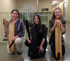 Harp Instructor Angela Biggs with students from the Hands On Harps workshop. In the Background, wire tree sculpture by WCCMA's Opus Arts Group artist Randy Adams.